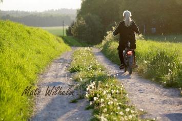 Ung kvinna på moped i motljus på åkerväg. Uppland. Foto: Mats Wilhelm / Naturfotograferna / IBL Bildbyrå.